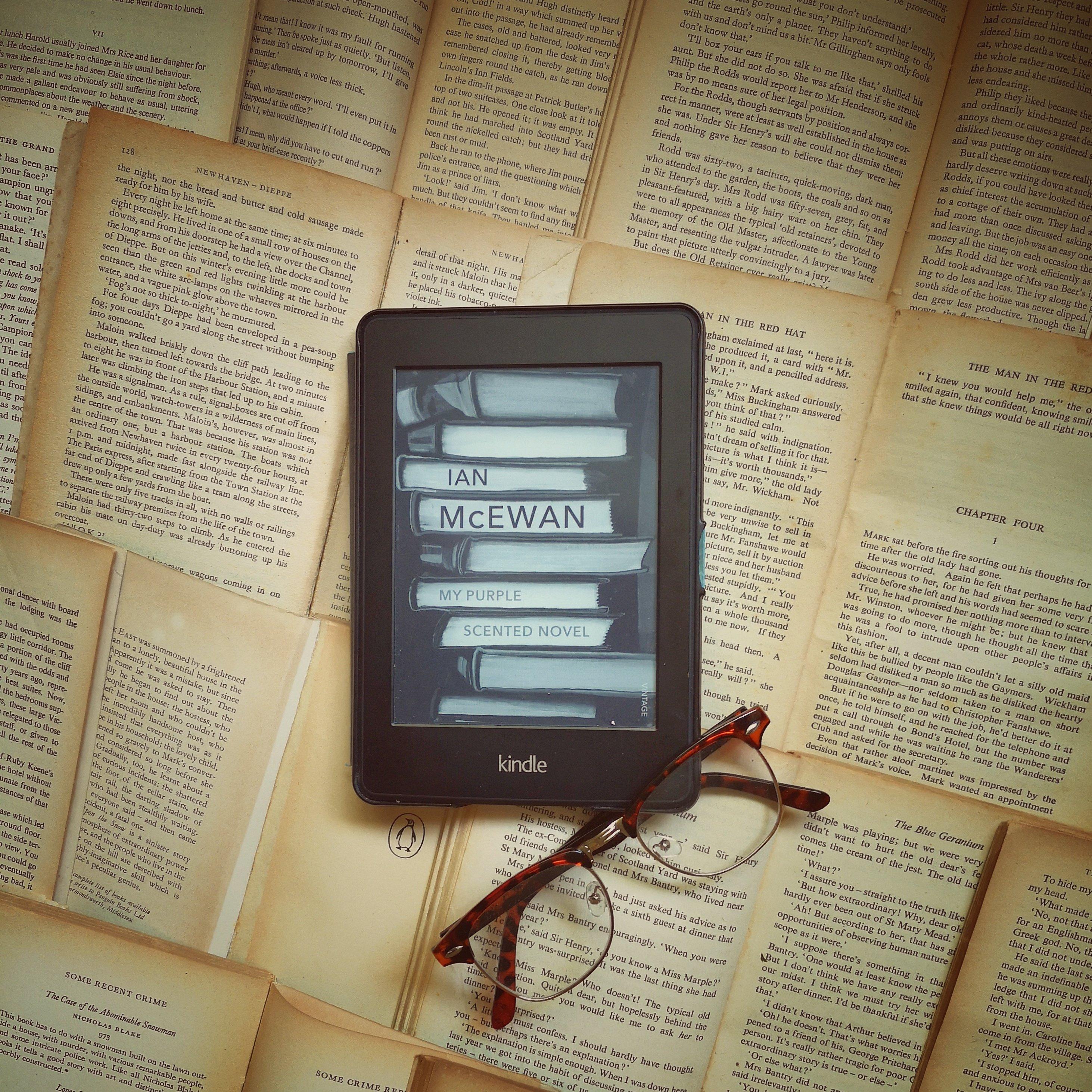 Kindle and glasses on vintage books