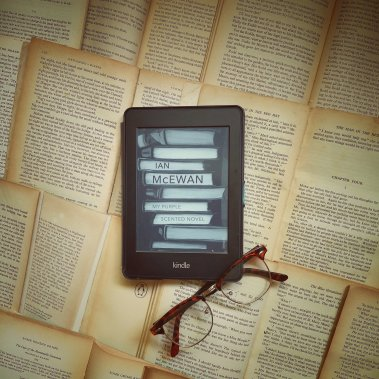 Kindle and glasses on vintage books