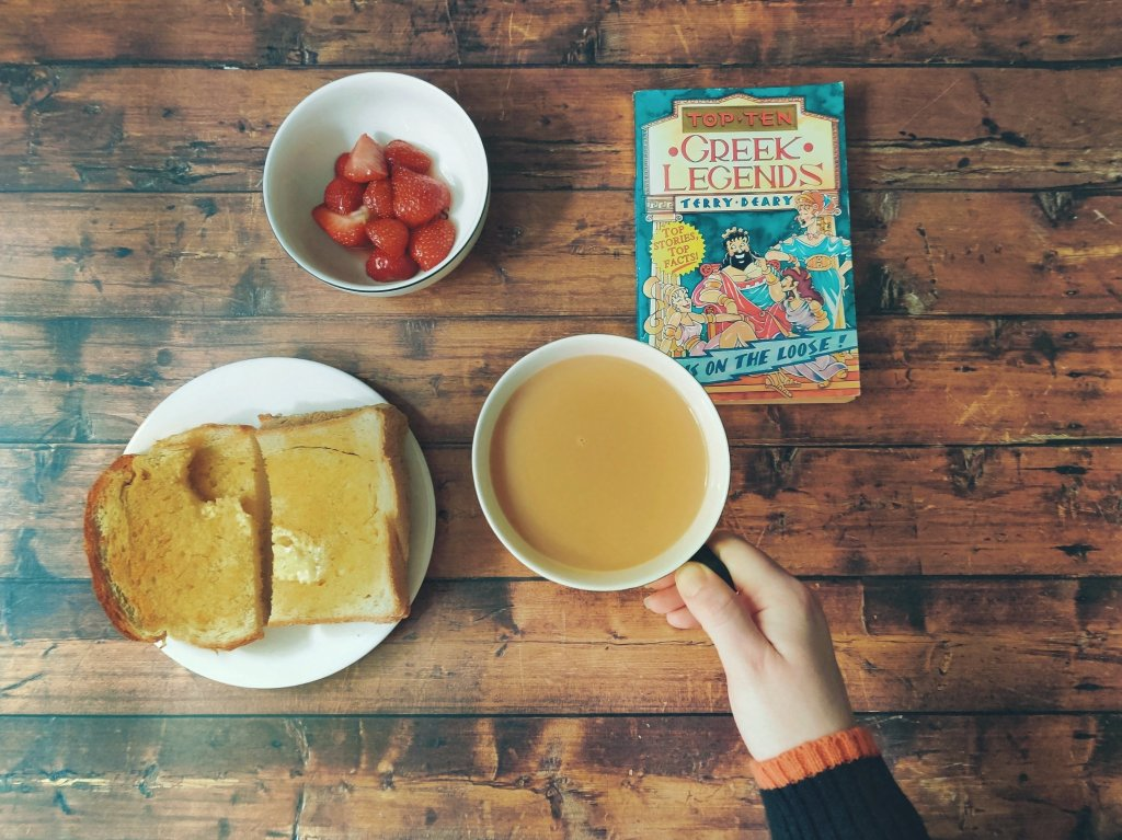 Hand holding teacup, a plate of toast, a bowl of strawberries and the book Top Ten Green Legends by Terry Deary